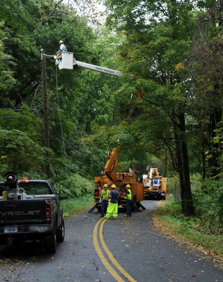 Spring House Road was closed Thursday afternoon, Sept. 30, 2010, while utility and Greenwich town workers fixed the snapped wires brought down by a tree falling on the road during the winds and rain. Photo: Helen Neafsey / Greenwich Time