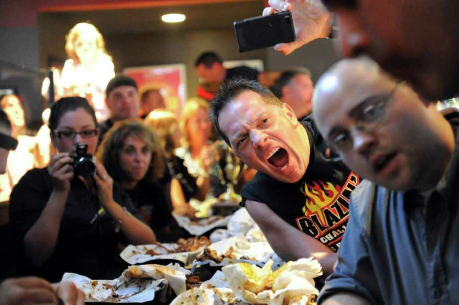 Firefighter Jimmy Tarzia hollers at a teammate as city police officers and firefighters square off in the Guns-n-Hoses Blazin Wing Eating Contest at Buffalo Wild Wings on Summer Street Thursday, September 30, 2010. Ten-percent of sales went to the American Lung Association and donations were collected for the two Bridgeport firefighters killed in action this summer. Photo: Keelin Daly / Stamford Advocate
