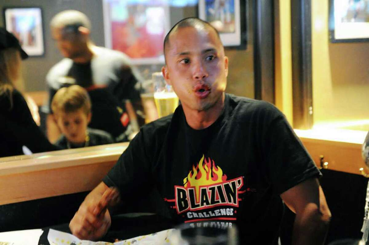 Police officer Mike Ngyen fights the heat as city police officers and firefighters square off in the Guns-n-Hoses Blazin Wing Eating Contest at Buffalo Wild Wings on Summer Street Thursday, September 30, 2010. Ten-percent of sales went to the American Lung Association and donations were collected for the two Bridgeport firefighters killed in action this summer.