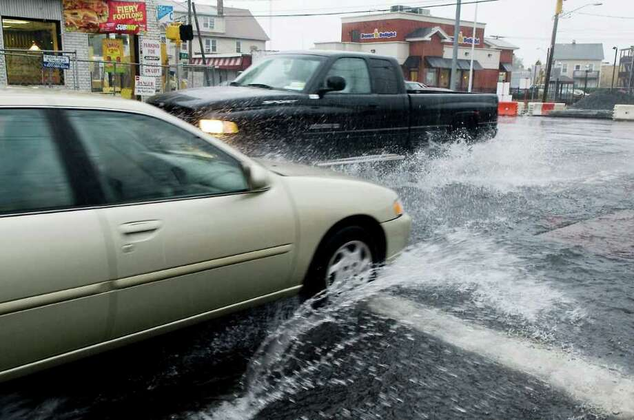 Cars plow through puddles at the corner of Myrtle Avenue and Elm Street as heavy rain falls in Stamford, Conn. on Friday October 1, 2010. Photo: Kathleen O'Rourke / Stamford Advocate