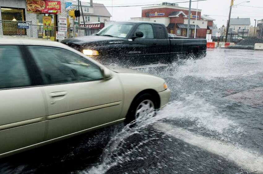 Cars plow through puddles at the corner of Myrtle Avenue and Elm Street as heavy rain falls in Stamford, Conn. on Friday October 1, 2010.