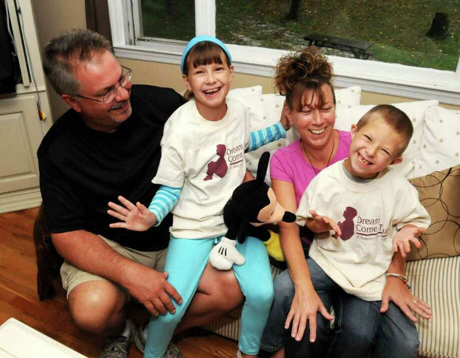 From left, the Dawson family of New Milford, Michael, Emily, 9, Gail and Connor, 8, have been given a trip to Orlando Fla. from the Dream Come True Foundation of Western, Connecticut. Connor has a congenital heart defect and his wish was to meet Barney the purple dinosaur. Pictured here in their home on Thursday Sept. 30, 2010. Photo: Lisa Weir / The News-Times Freelance