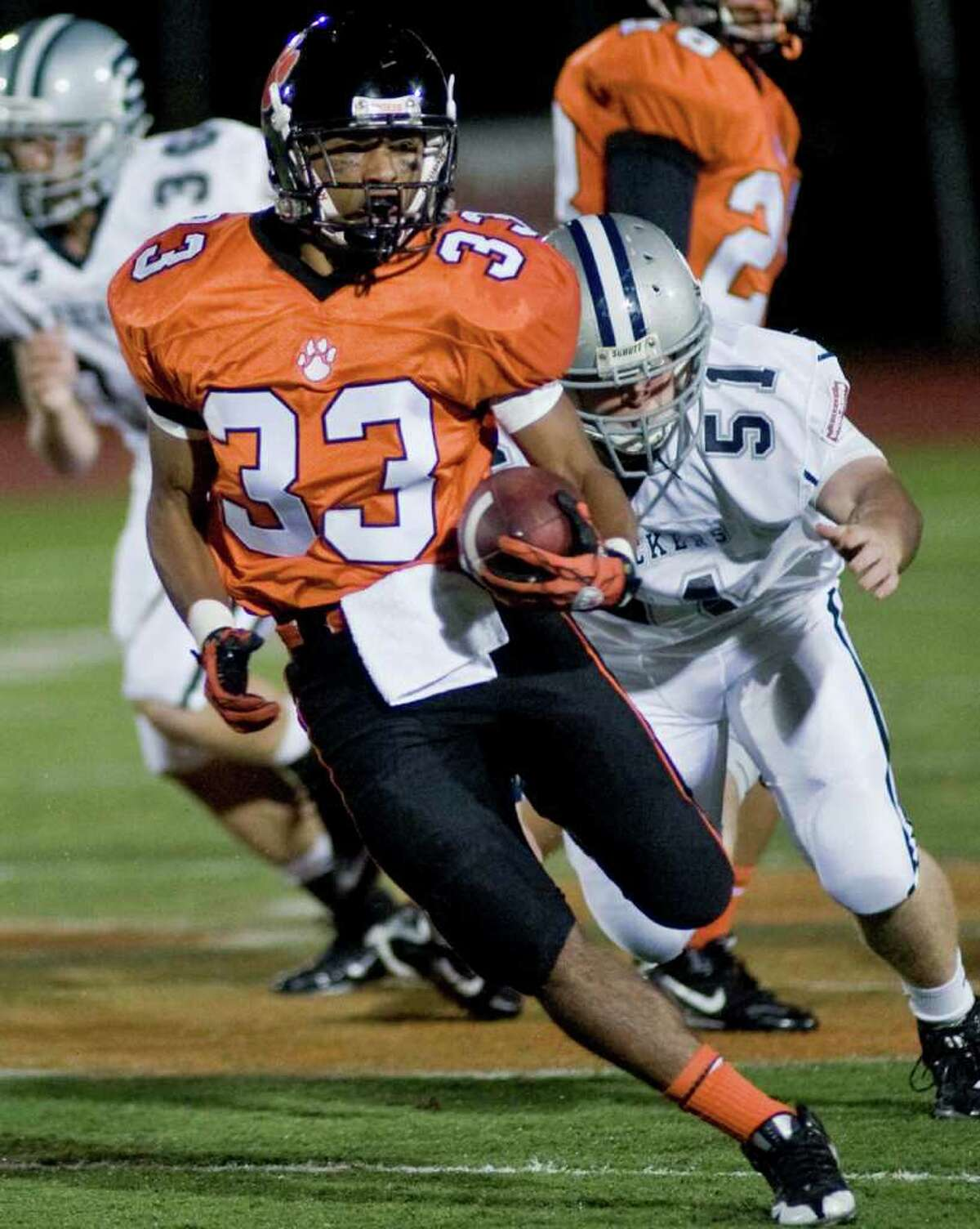 Ridgefield's Bryan Jimenez cuts to avoid Staples' Mike Giunta during a football game at Ridgefield. Friday, Oct. 1, 2010