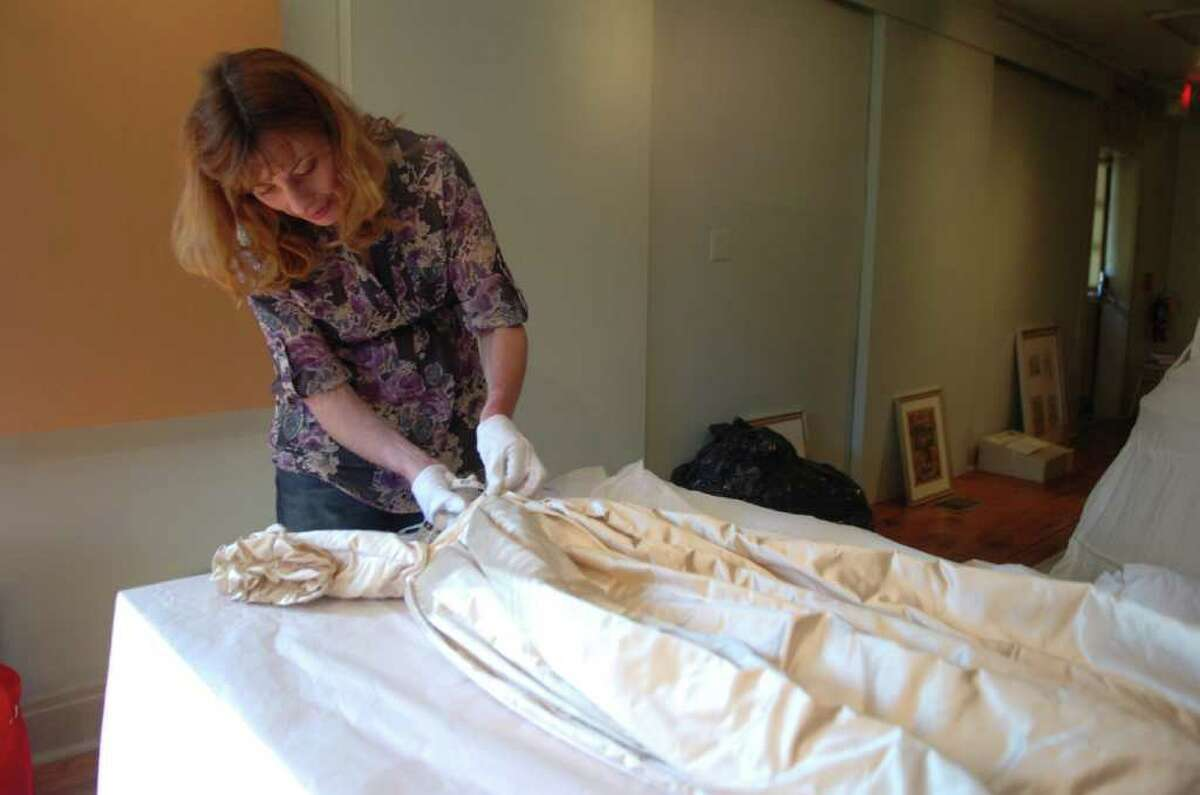 Adrienna Saint-Pierre, of Redding, measure the waist of an 1860 bridal gown in preparation for the Greenwich Historical Society's
