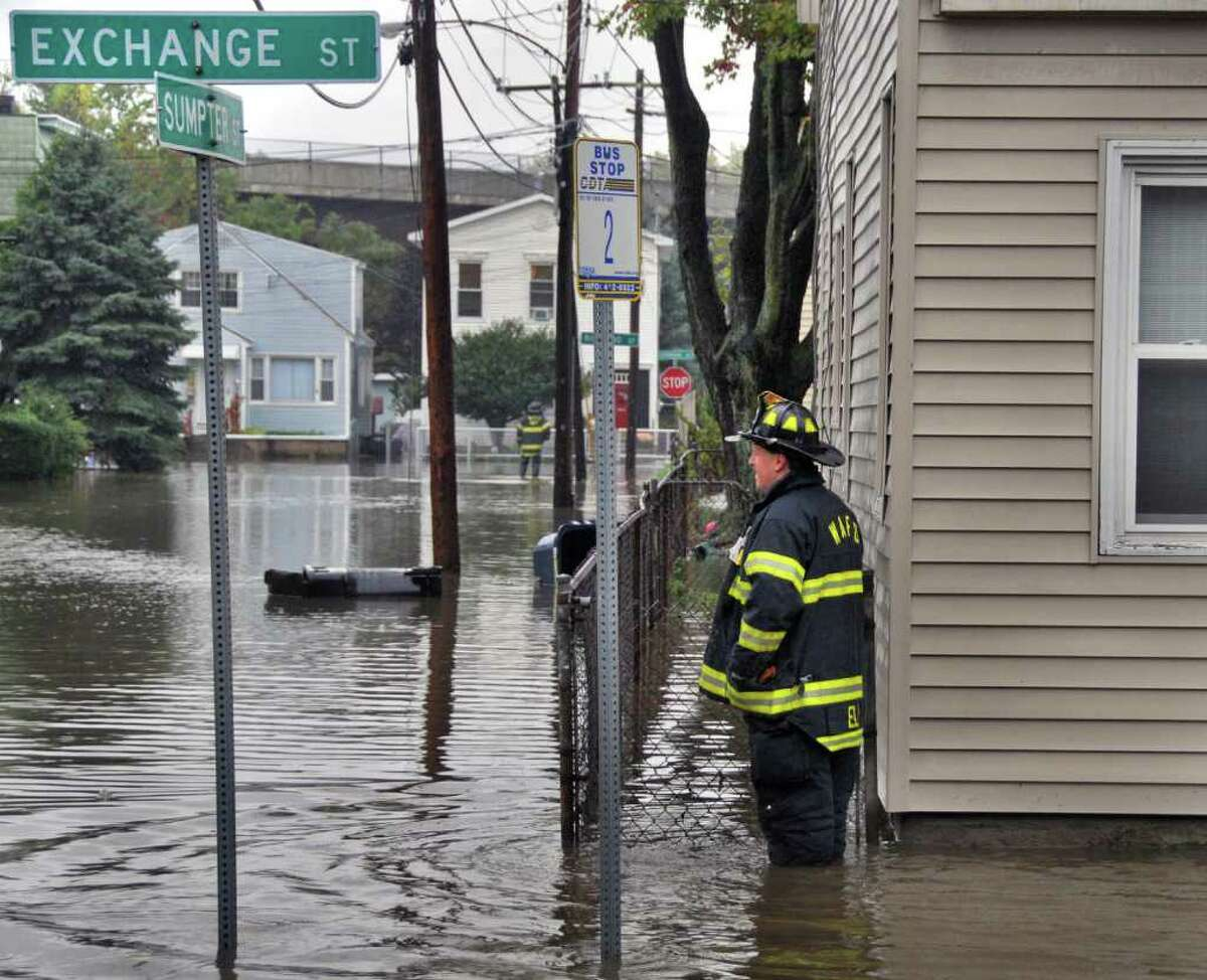 West Albany firefighters survey flooded homes at Exchange and Sumpter streets in Colonie in 2010. (John Carl D'Annibale / Times Union