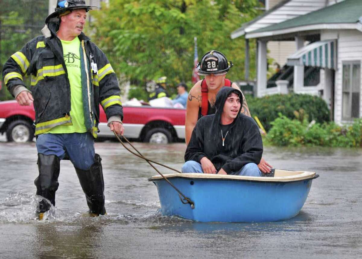 Sumpter Street resident Anthony Catalano is helped from his flooded home by West Albany firefighters Brian Elk, left, and Bill Mencel in 2010. Catalano opposes a senior housing development in 2020 that he says will increase flooding risks. (John Carl D'Annibale / Times Union)