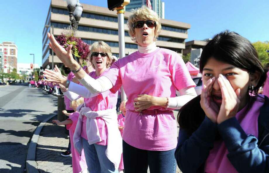 "Sheila McCaffrey (center) encourages drivers to honk their horns as supporters and breast cancer survivors gather along Atlantic Street to create a ""Mile of Pink"" in downtown Stamford. The third annual ""Mile of Pink"" is a 90-minute show of unity and a demonstration of breast cancer awareness. The event kicks off Stamford Hospital's month-long annual ""Paint the Town Pink"" campaign in Stamford, Conn. on Saturday October 2, 2010. Photo: Kathleen O'Rourke / Stamford Advocate"