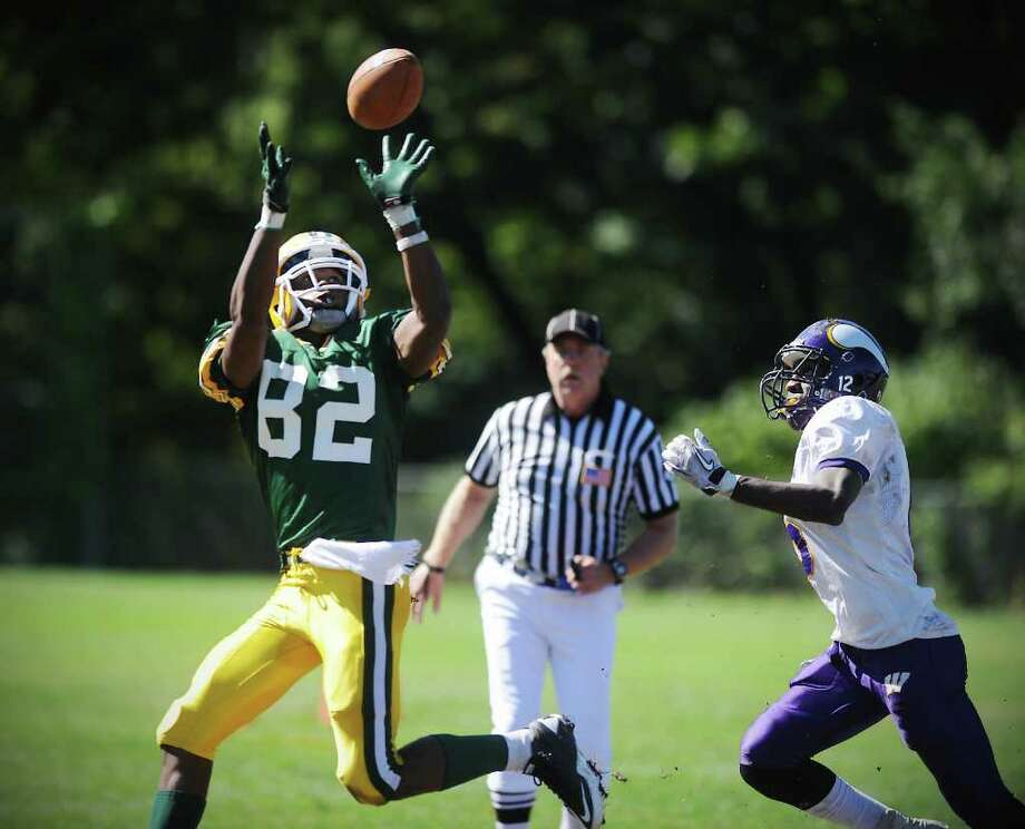 Trinity Catholic High School's Shawn Robinson reaches for the ball and runs it in for a touchdown against  Westhill High School's Zack Emilcar in city rivalry football action at Trinity in Stamford, Conn. on Saturday October 2, 2010. Photo: Kathleen O'Rourke / Stamford Advocate