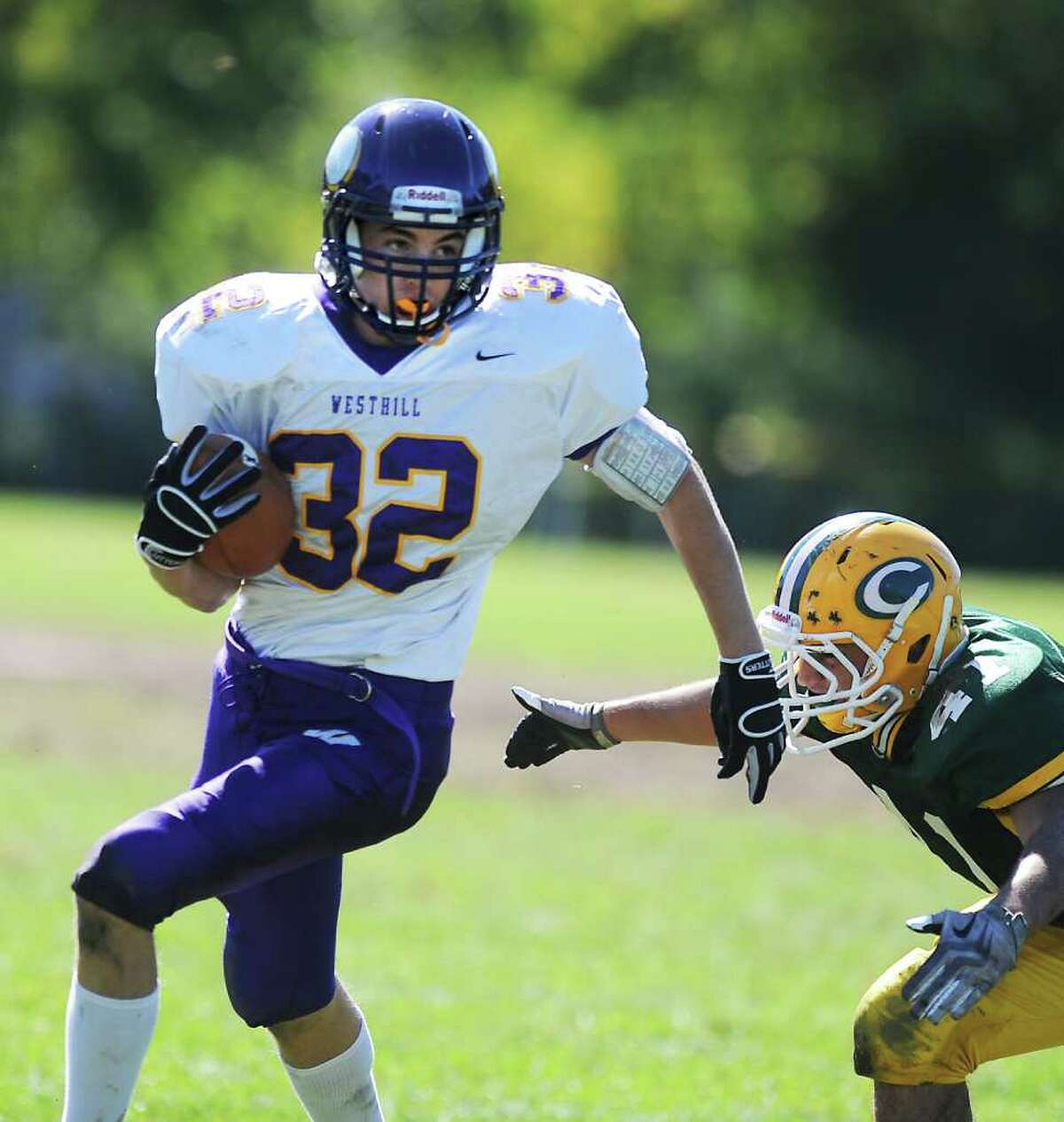 Westhill High School's David Engel carries the ball against Trinity Catholic High School's Tyler Zaro in city rivalry football action at Trinity in Stamford, Conn. on Saturday October 2, 2010.