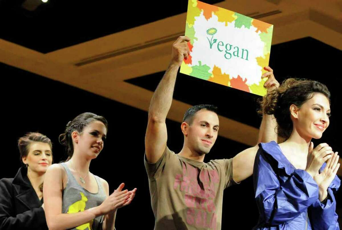Joey Leo holds up a vegan sign as he and other models walk the runway in animal free clothing during a vegan fashion show as part of the Vegetarian Expo at the Empire State Plaza. (Michael P. Farrell / Times Union)