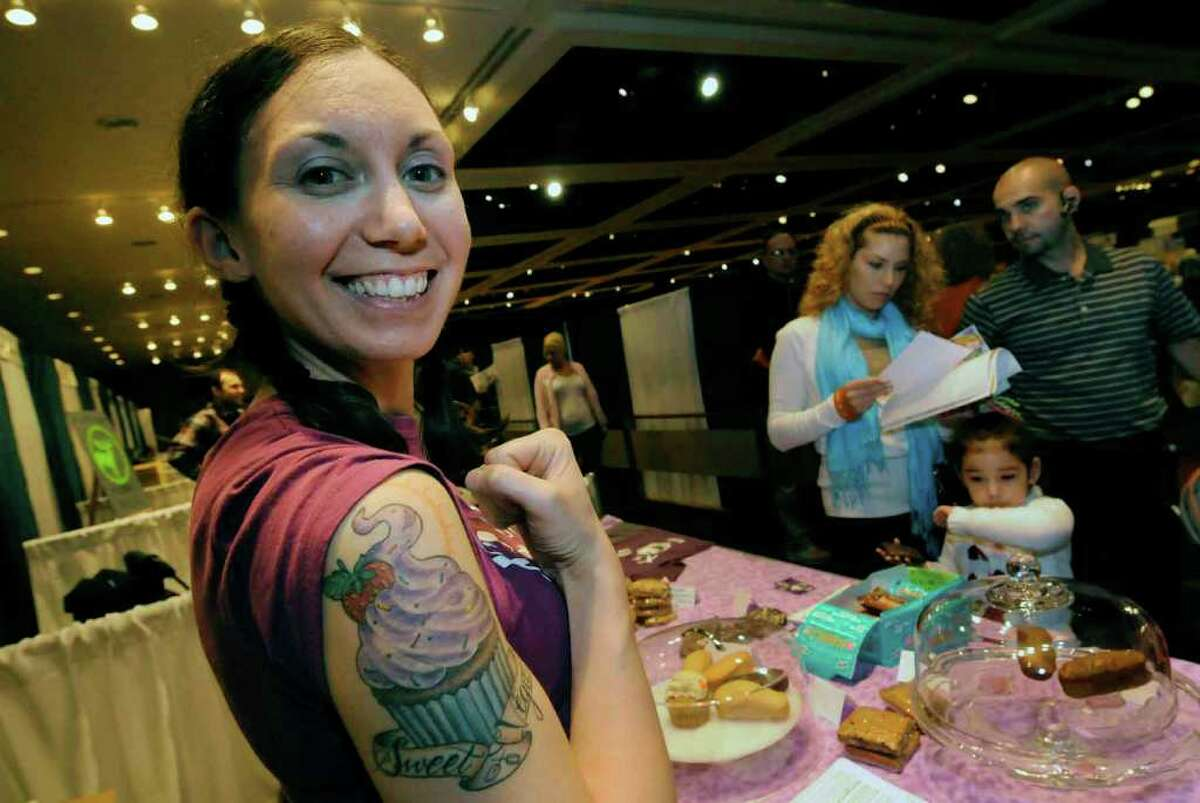 Sarah Preston owner of X's to O's Vegan Bakery shows off her cupcake tattoo that reads