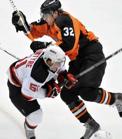 David McIntyre, left, a former Colgate University player who scored two goals for the Albany Devils on Saturday night, mixes it up with the Adirondack Phantoms' Jesse Dudas during the Devils' 4-2 victory in an American Hockey League exhibition contest played at Houston Field House on the Rensselaer Polytechnic Institute campus in Troy.  (John Carl D'Annibale / Times Union) Photo: John Carl D'Annibale / 00010220A