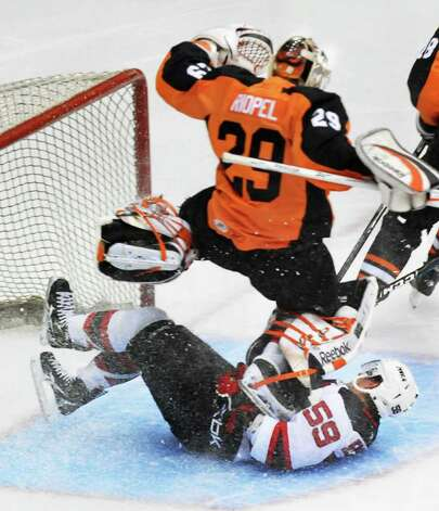 The Albany Devils' Adam Henrique slides into the goal under Adirondack Phantoms goalie Nic Riopel during Saturday night's American Hockey League exhibition game, played Houston Field House on the Rensselaer Polytechnic Insitute campus in Troy. The Devils won 4-2. (John Carl D'Annibale / Times Union) Photo: John Carl D'Annibale / 00010220A