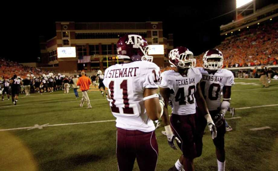 Texas A&M's Jonathan Stewart (from left), Von Miller and Sean Porter linger on the field in Stillwater, Okla., after the Aggies' 38-35 loss to Oklahoma State on Thursday. A&M's defense has five sacks in four games. Miller had 17 last season.