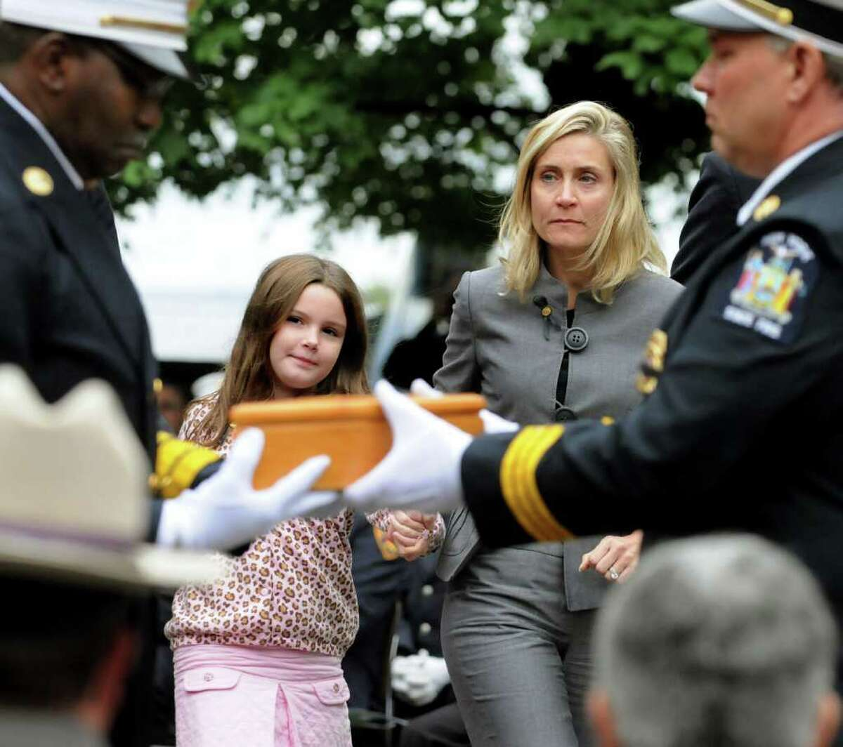 Tara Joyce of Eastchester, whose husband, Patrick Joyce Jr., died fighting a fire last October in Yonkers, and their daughter Isabella, 8, receive flags at the Fallen Firefighters Memorial Ceremony on Tuesday at the Empire State Plaza in Albany. The ceremony honored nine firefighters who gave their lives in the line of duty. Of the firefighters added to the wall, seven died in 2009 and the other two are from previous years. There are now 2,357 names on the wall. (Cindy Schultz / Times Union)t. (Cindy Schultz / Times Union)