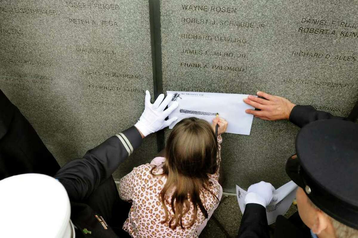 Isabella Joyce, 8, makes a copy of the engraved name of her father, Patrick Joyce Jr., with the help of Yonkers firefighters Dominick Fornabaio, left, and John Pyrch at the Fallen Firefighters Memorial Ceremony on Tuesday at the Empire State Plaza in Albany. Joyce died a year ago fighting a Yonkers fire. (Cindy Schultz / Times Union)