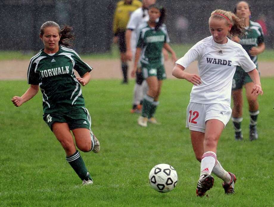 Fairfield Warde's Maggie Allen dribbles the ball away from Norwalk's Emily Pullen during Tuesday's game at Fairfield Warde High School on October 5, 2010. Photo: Lindsay Niegelberg / Connecticut Post