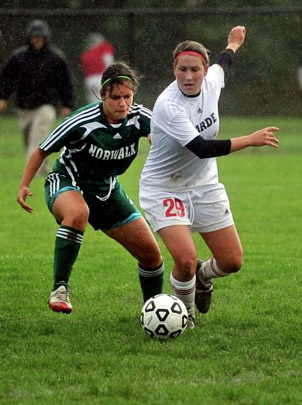 Norwalk's Melissa Rojo, left, and Fairfield Warde's Taylor Bargmann, right, compete for control of the ball during Tuesday's game at Fairfield Warde High School on October 5, 2010.