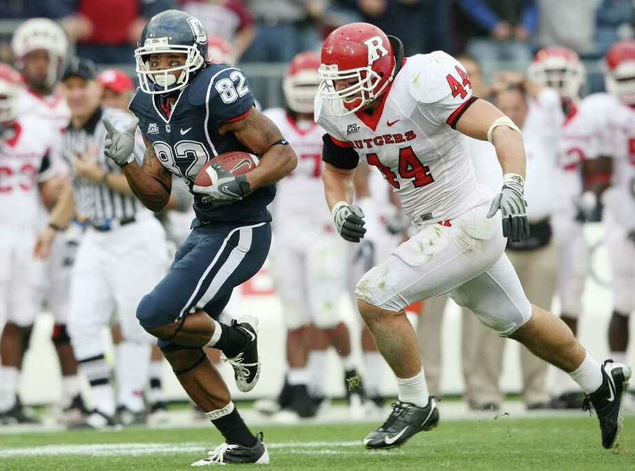 EAST HARTFORD, CT - OCTOBER 31:  Kashif Moore #82 of the Connecticut Huskies carries the ball as Ryan D'Imperio #44 of the Rutgers Scarlet Knights defends on October 31, 2009 at Rentschler Field in East Hartford, Connecticut. Rutgers defeated Connecticut 28-24.  (Photo by Elsa/Getty Images) *** Local Caption *** Kashif Moore;Ryan D'Imperio Photo: Elsa, Getty Images / 2009 Getty Images