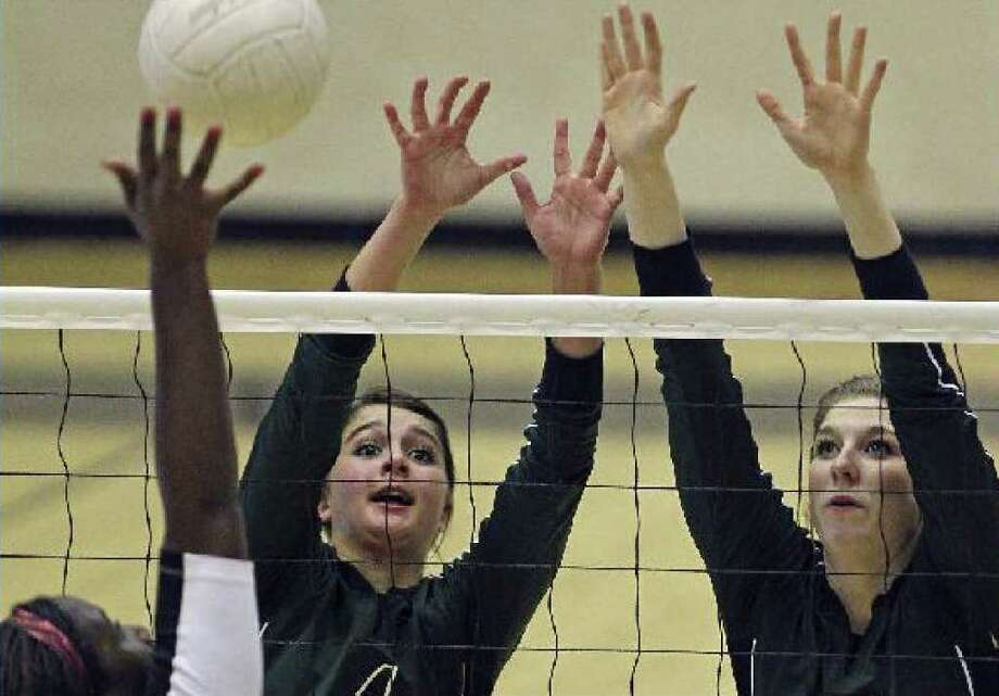Reagan's Morgan Reed (back left) and Alyssa Adams defend Churchill's Deveney Wells-Gibson on Tuesday night at Littleton Gym. Reagan won the 26-5A match in four games.
