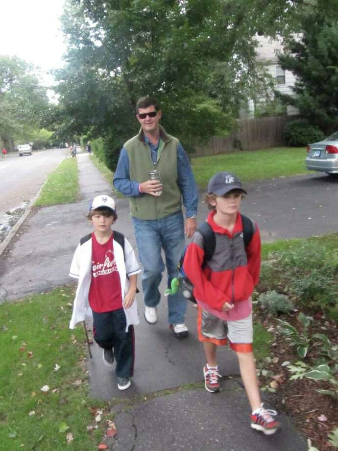 "Jon Wheeler (wearing sunglasses) walks his children Connor (left) and Jack (right) to Sherman Elementary School Wednesday morning. Sherman was celebrating its 10th annual ""Walk A Child To School Day."" Photo: Kirk Lang / Fairfield Citizen"