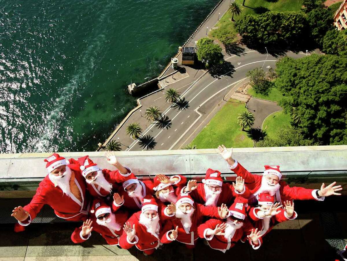 SYDNEY, AUSTRALIA - OCTOBER 06: Volunteers dressed as Santa stand atop the southern pylon of the Sydney Harbour bridge to launch the Variety Santa Fun Run at Sydney Harbour Bridge on October 6, 2010 in Sydney, Australia. The Variety Children's Charity will host the November 28, five kilometre run to raise funds for Australian children with special needs. Organisers hope the race will attract over 14,000 runners to break the world 'Santa Run' record currently held by Portuagal. (Photo by Graham Denholm/Getty Images)