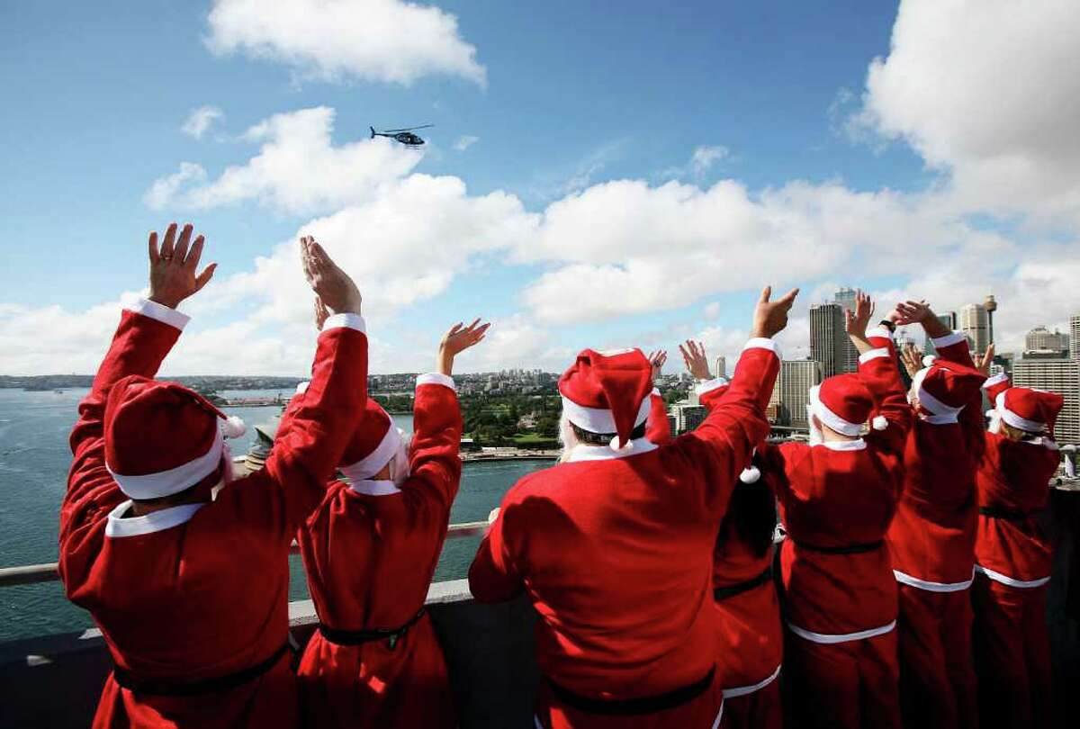 SYDNEY, AUSTRALIA - OCTOBER 06: Volunteers dressed as Santa wave at a tv news helicopter as they stand atop the southern pylon of the Sydney Harbour bridge to launch the Variety Santa Fun Run at Sydney Harbour Bridge on October 6, 2010 in Sydney, Australia. The Variety Children's Charity will host the November 28, five kilometre run to raise funds for Australian children with special needs. Organisers hope the race will attract over 14,000 runners to break the world 'Santa Run' record currently held by Portuagal. (Photo by Graham Denholm/Getty Images)