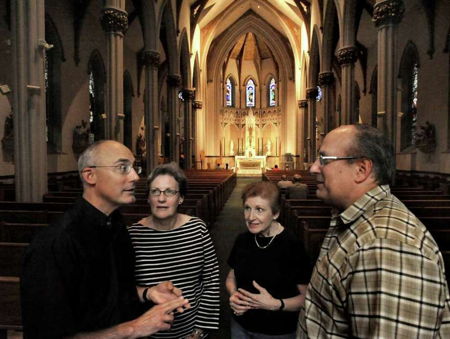 Rev. Gregg Meca, left, talks with parishioners in St. Peter's Church, in Danbury, Friday, Oct. 1, 2010. Standing left of center is Barbara Lynch, Therese Ruppert, center and Dominic Ciliberto, right. Photo: Michael Duffy / The News-Times