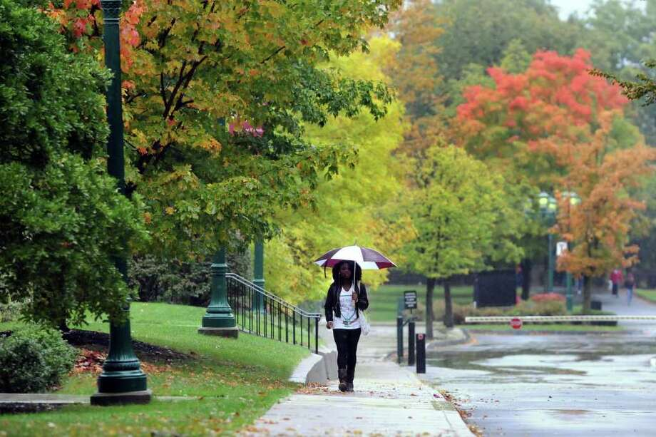 A pedestrian shields herself from the rain as she walks across campus on Wednesday, Oct. 6, 2010, at Union College in Schenectady, N.Y. (Cindy Schultz / Times Union) Photo: Cindy Schultz