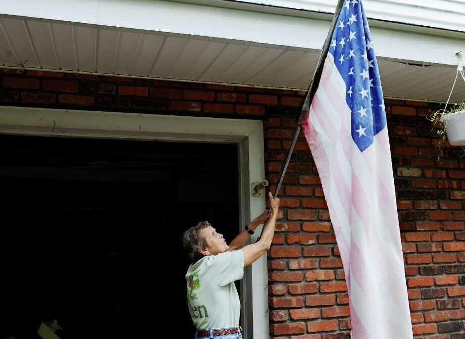 Janet Triplett untangles her flag on the front of her house on Stillwater Road in Stamford, Conn. on Wednesday October 6, 2010.  Triplett's driveway was damaged by heavy rains and pour drainage on the road in last week's storm. Photo: Kathleen O'Rourke / Stamford Advocate