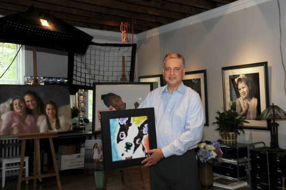 Richard Flaskgaar, in his new photo studio, named after his first subject, his dog Jack, who is also in the picture he holds, on Sept. 29, 2010. Photo: Helen Neafsey / Greenwich Time