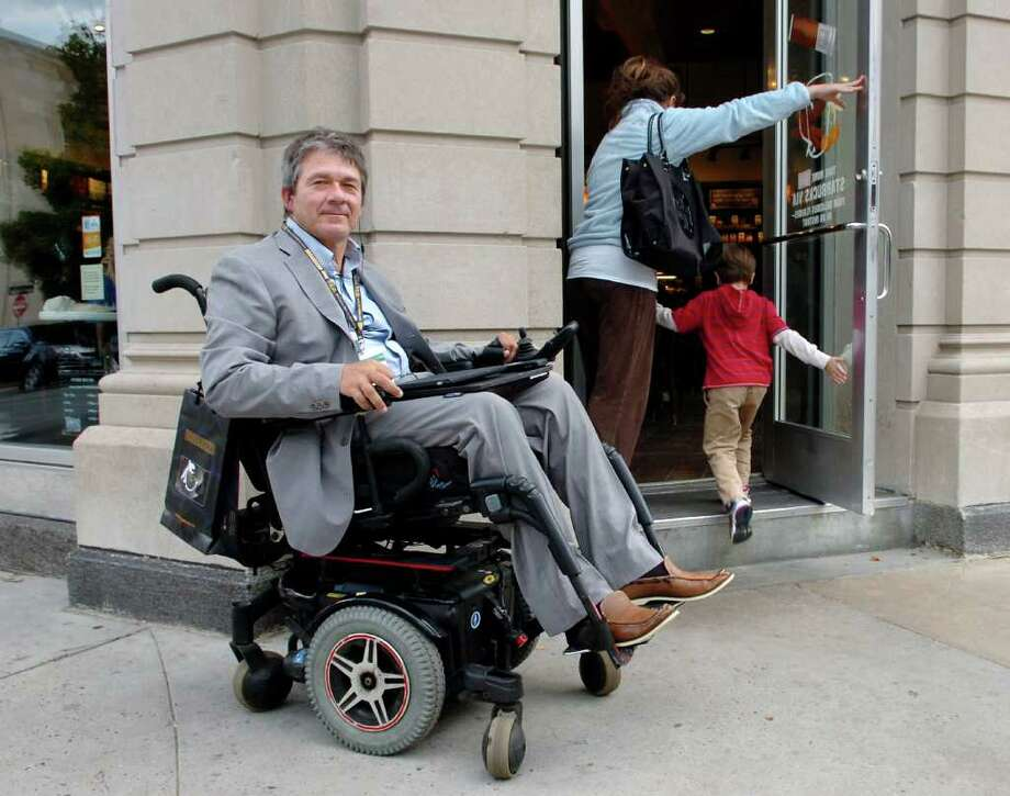 Luigi Girotto of Rye, N.Y., poses by the entrance to the Greenwich Avenue Starbucks coffee shop, early Wednesday evening, Oct. 6, 2010.  The recently renovated store does not include wheelchair access and Girotto, who said he is a fan of Starbucks coffee and a weekend visitor to Greenwich Avenue, is upset. Photo: Bob Luckey / Greenwich Time