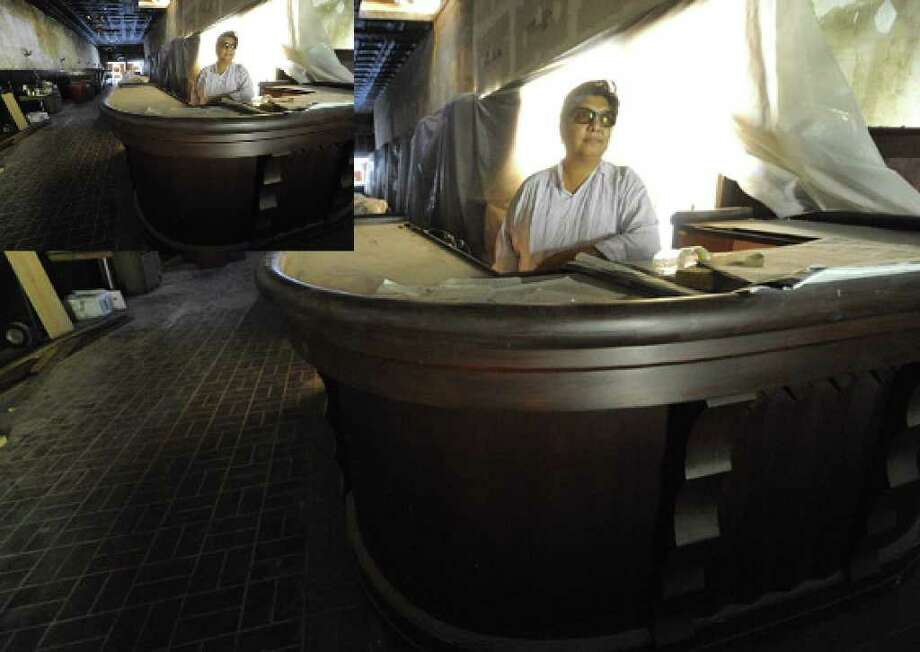 Sondra Alfaro stands behind the large bar in the Esquire Tavern in downtown San Antonio. After being closed since 2006, it  is expected to open in January after it gets a makeover.