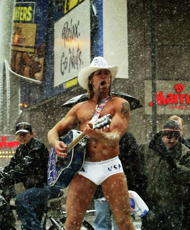 "NEW YORK - DECEMBER 5: Robert John Burck, who calls himself ""The Naked Cowboy"" plays his guitar in Times Square December 5, 2002 in New York City.  New York City may get up to eight inches of snow in an early East Coast storm that has closed schools throughout the area and left six people dead in traffic accidents.  (Photo by Robert Giroux/Getty Images) Photo: Robert Giroux, Getty Images / 2002 Getty Images"