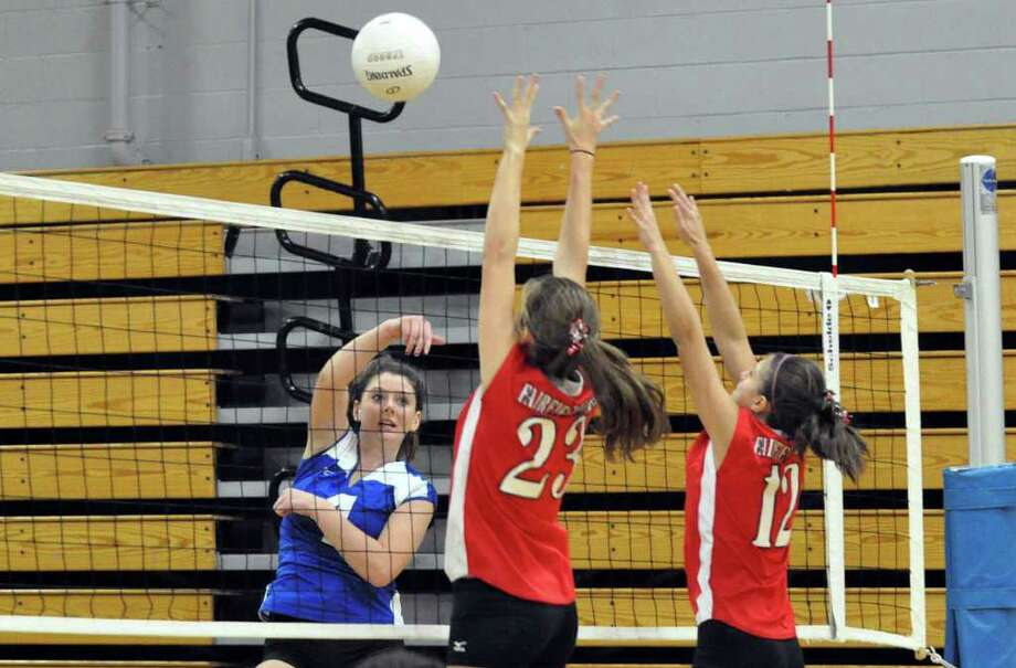 Fairfield Ludlowe's Dillon Casey hits the ball over the net as Fairfield Warde's Angie Walker and Tatiana Fernandes set up a block during the girls volleyball game at Ludlowe on Wednesday, Oct. 6, 2010. Photo: Amy Mortensen / Connecticut Post Freelance