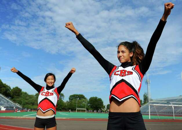 Central High School cheerleaders, junior Tedah Chan, left, and senior Heidi Medina, strike a pose in the team's new uniforms Wednesday Sept. 29, 2010 at Kennedy Stadium in Bridgeport, Connecticut.  The cheerleading squad is not happy with the uniforms which they say are illfitting and violate league rules because the tops reveal middriff. Photo: Autumn Driscoll / Connecticut Post