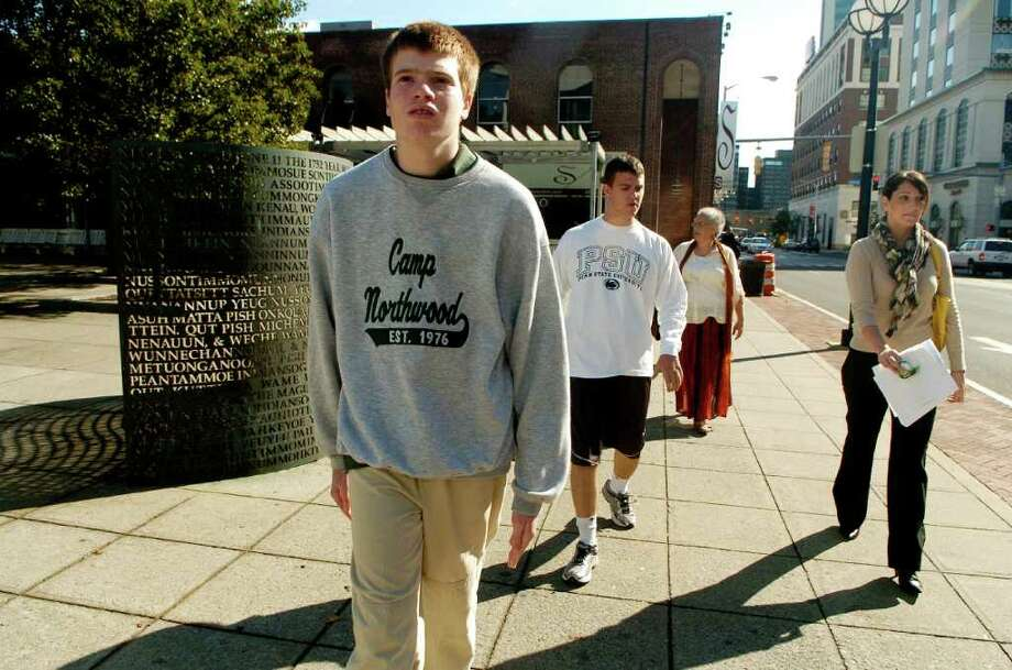 Karl Arrezzini and Oliver Moore students at Abilis program called LIFE (Lifeskills Independence Friendships and Employment) which helps 18-24 year-olds on the autism spectrum transition from high school into adult life, walk with instructors Regina Cornelio and Sue Izeman after handing out flyers to local businesses for Autism walk in Stamford, Conn. on Thursday October 7, 2010. Photo: Dru Nadler / Stamford Advocate Freelance