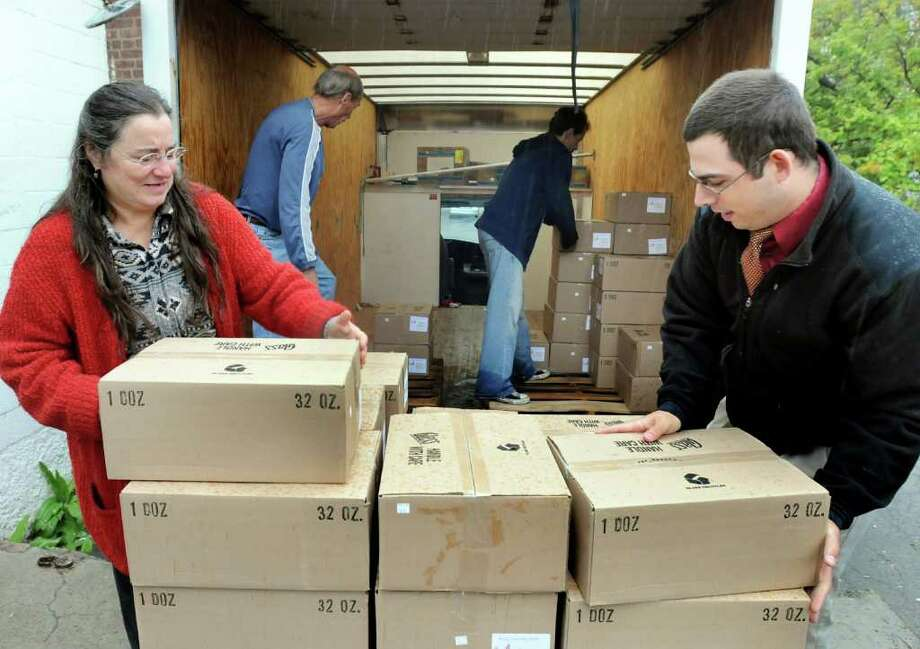 Deb Catozzi and Vincent Ross, right, of Hunger Action Network unload boxes of spaghetti sauce with the help of Bruce Carolus, center left, and Bob Donahue of Schenectady Inner City Ministry on Wednesday, Oct. 6, 2010, at Schenectady Inner City Ministry in Schenectady, N.Y. The Hamilton Hill Food Processing Project made the donation of 100 cases of sauce. Hunger Action Network started HHFP three years ago to improve nutrition in low-income neighborhoods, provide jobs and help provide a market for local farmers. (Cindy Schultz / Times Union) Photo: Cindy Schultz
