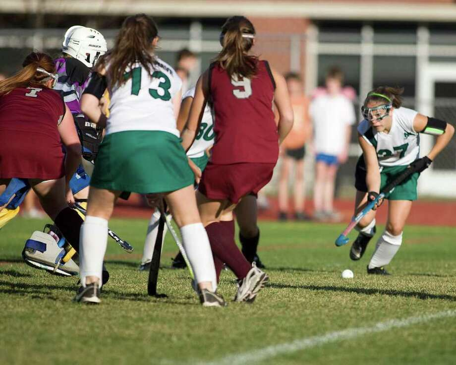 With the defense packed in tight and her teammates looking for a pass or a rebound, New Milford's Kelsey Heaton (37)  sets up a shot during an SWC field hockey game won by the Green Wave, 2-1, in overtime over Pomperaug Monday at New Milford High. Photo: Barry Horn / The News-Times Freelance