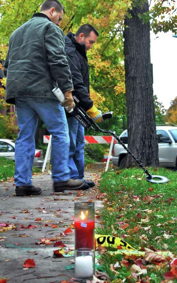 The Albany Police Forensic Unit's Mark Sauter, left, and Victor Pizzola search for evidence near the makeshift memorial for UAlbany student Richard Bailey, who was shot and killed October 22, 2008, near the corner of Yates and South Lake in Albany. (Times Union archive/John Carl D'Annibale) Photo: John Carl D'Annibale