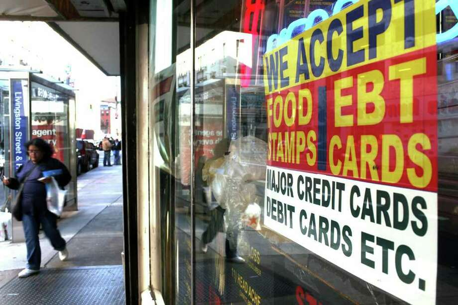 A sign in a market window advertises the acceptance of food stamps in New York City. New York Mayor Michael Bloomberg is proposing an initiative that would prohibit New York City's 1.7 million food stamp recipients from using the stamps, a subsidy for poor residents, to buy soda or other sugary drinks. Bloomberg, joined by Gov. David Paterson, has stressed that obesity among the poor has reached critical levels. (Photo by Spencer Platt/Getty Images) Photo: Spencer Platt / 2010 Getty Images