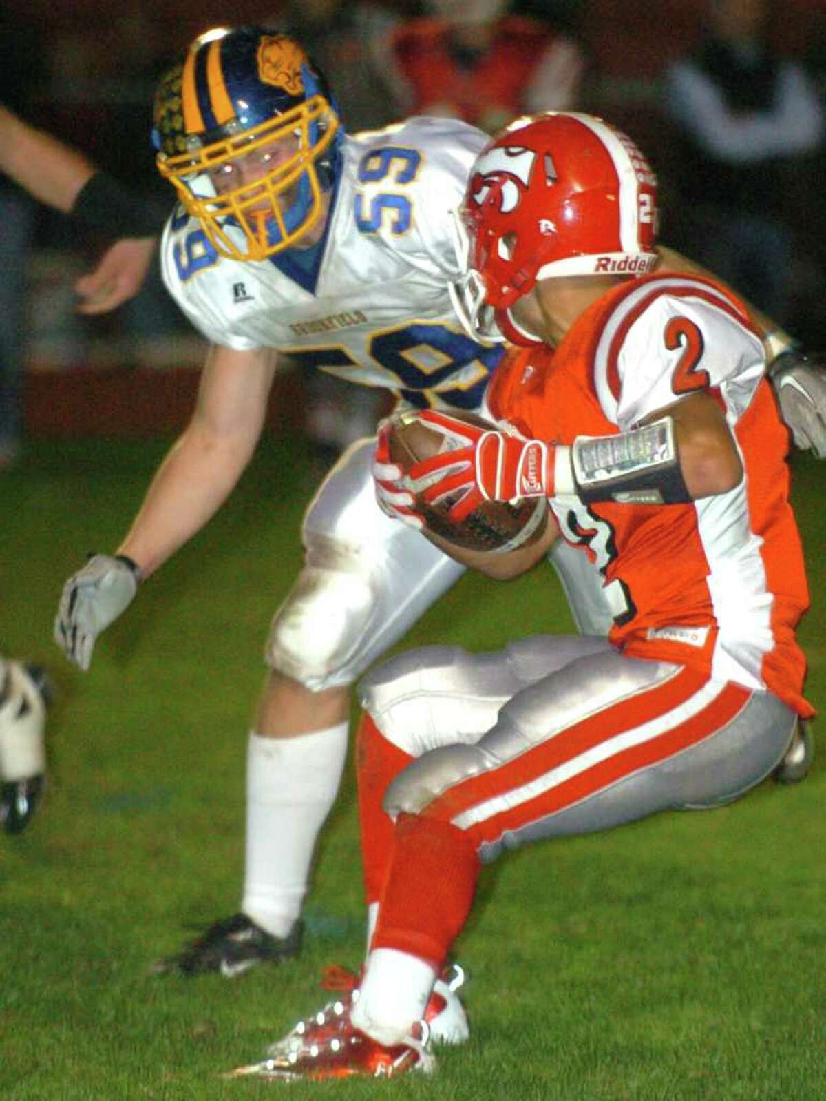 Masuk's 2, Tyler Perimenis, sets up for a pass while Brookfield's 59, Tyler Heckmann, blocks during the football game against Brookfield at Masuk Oct. 8, 2010.