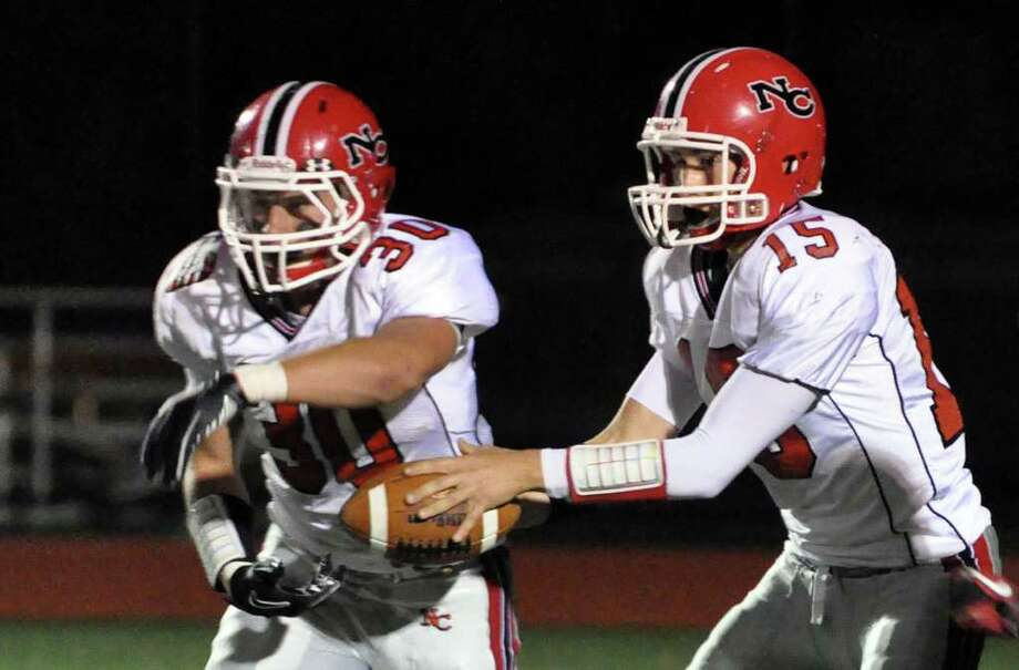New Canaan's Matthew Milano fakes a handoff to Conor Goodwin during the football game against Fairfield Warde at Warde on Friday, Oct. 8, 2010. Photo: Amy Mortensen / Connecticut Post Freelance