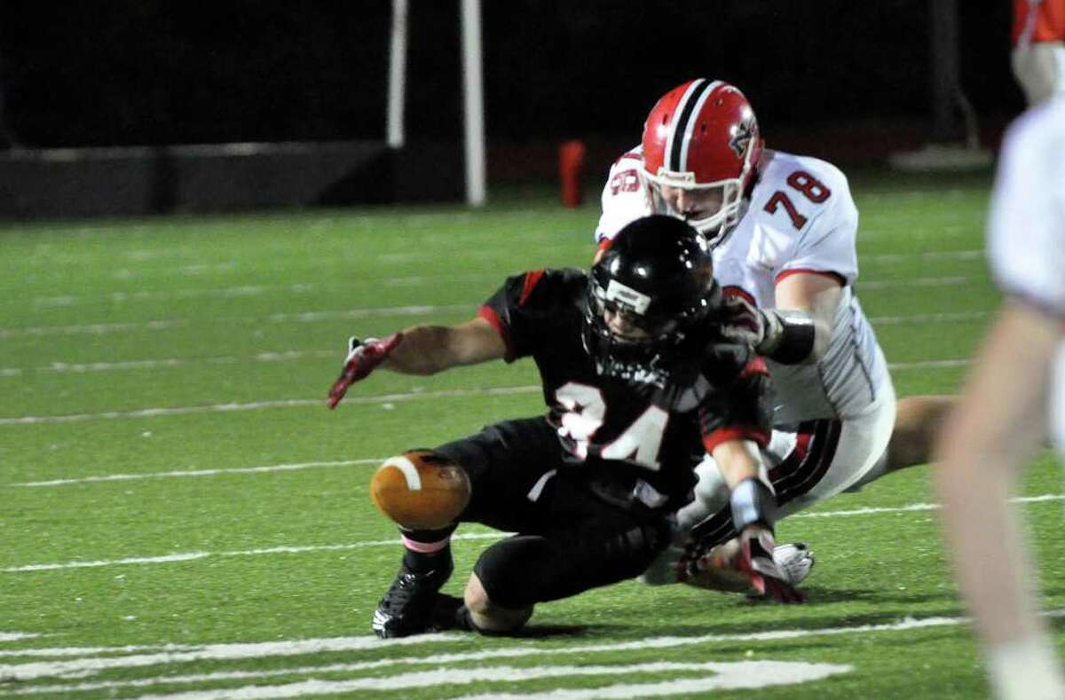Fairfield Warde's David Wolff and New Canaan's Conor Hanratty chase after a fumbled ball during the football game at Warde on Friday, Oct. 8, 2010.