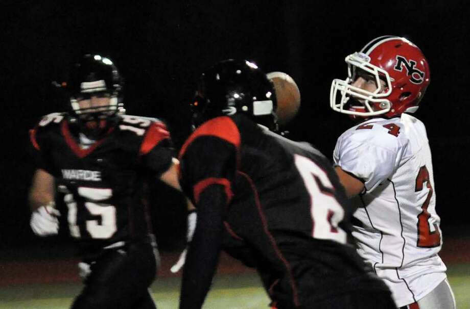 New Canaan's Patrick Newtown carries the ball between Fairfield Warde defensemen Will Halliday and Terrell Walden during the football game at Warde on Friday, Oct. 8, 2010. Photo: Amy Mortensen / Connecticut Post Freelance