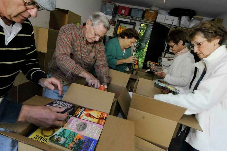 Volunteers, from left, Richard Sheftic, Bill Schweitzer, Karen Layman, Ellen Keegan and Judy Schweitzer pack donated books to be sent to troops in Afghanistan and Iraq from Keegan's garage in Clifton Park. (Michael P. Farrell / Times Union) Photo: Michael P. Farrell