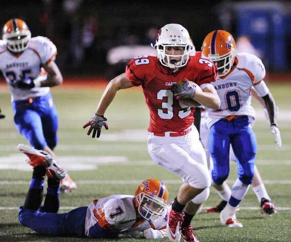 GHS running back Mike Daly, # 39, breaks away from Danbury High School  player Anthony Nejame, # 7, bottom,  and Daryle-Michael Dennis, # 10, right, during game between the Greenwich High School football team vs. the Danbury High School football team, at Greenwich High School, Friday evening, Oct. 8, 2010. Photo: Bob Luckey / Greenwich Time