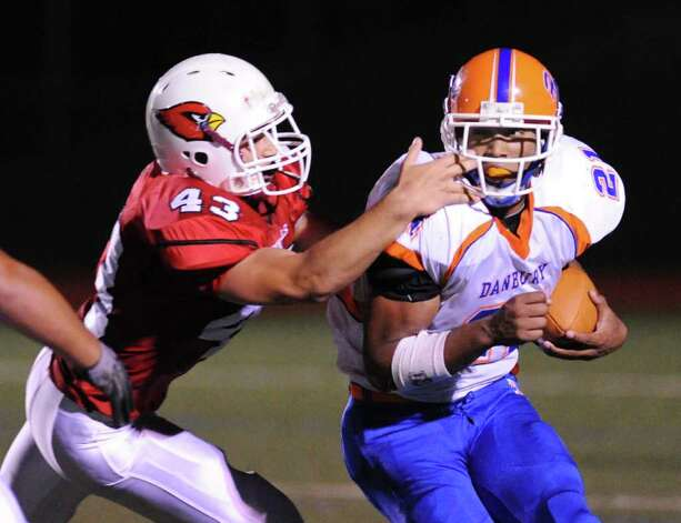 Ben Cecci, # 43 of GHS, left,  puts his hand through the face-mask of running back Deyon Rosado, # 21 of Danbury High School, right, on a tackle attempt during game between the Greenwich High School football team vs. the Danbury High School football team, at Greenwich High School, Friday evening, Oct. 8, 2010.  No penalty was called on the play. Photo: Bob Luckey / Greenwich Time