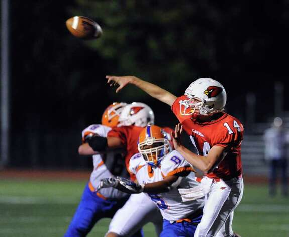 GHS quarterback Liam O'Neil # 14, throws as he is pressured by Sean Malone, # 8 of Danbury High School during game between the Greenwich High School football team vs. the Danbury High School football team, at Greenwich High School, Friday evening, Oct. 8, 2010. Photo: Bob Luckey / Greenwich Time