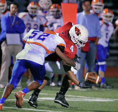 Receiver Kyle Camacho, # 4 of GHS, right, can not hold onto the ball as he is hit by Danbury's Marcus Dixon, # 52, during game between the Greenwich High School football team vs. the Danbury High School football team, at Greenwich High School, Friday evening, Oct. 8, 2010. Photo: Bob Luckey / Greenwich Time